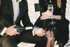 Messieurs dans un shampagne de versement d'équipement officiel dans son vin image stock