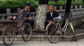 2 messieurs s'asseyant sur le côté de la route Image stock