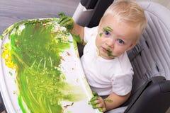 Портрет милого мальчика messily играя с красками стоковая фотография rf