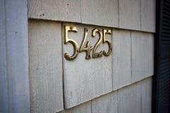 Messing nummer 5425 op een buitenmuur stock afbeelding