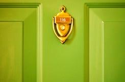 Messingklopfer-Grün-Tür Stockfoto