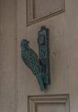 Messingskloppers in de vorm van een vogel op een room-gekleurde deur, a Stock Afbeelding