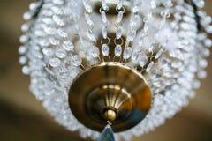 Messingskroonluchter met kristalkettingen die op plafond hangen stock fotografie