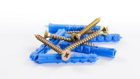 Messingsschroeven en blauwe plastic pennen die op vlakke oppervlakte liggen Stock Fotografie