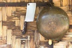 Messingwanne und hacken Messer, das an der gesponnenen Bambuswand hängt Lizenzfreies Stockfoto