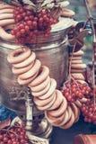 Messingweinlesesamowar, ein Bündel Bagel, rote Beeren, Äpfel als Symbol der russischen Gastfreundschaft Getontes Bild lizenzfreie stockfotos