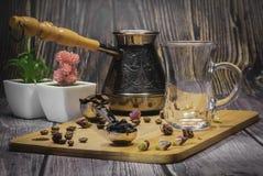 Messlöffel für Tee und Kaffee mit Kaffeebohnen und trockenen Teeblättern auf einer hölzernen Platte stockbild