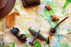 Messo per il viaggiatore, vista superiore La macchina fotografica, l'aeroplano e la bussola sono sulla mappa immagine stock