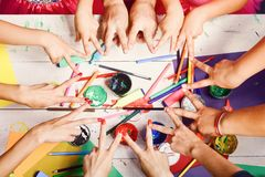 Messy art concept. Artists hands with stationery and colored paper. royalty free stock photos