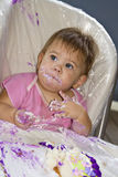 Messy baby with cake. Beautiful messy baby girl eating birthday cake with her hands Stock Photos