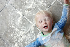 Messy Baby Covered in Baking Flour. A one year old small child is laying on a very messy kitchen floor, covered in white baking flour.  Room for text, copy space Stock Image