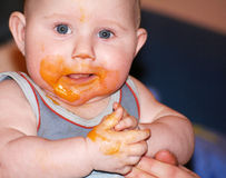 Messy baby after eating food. Baby boy after eating; face is covered with food stock photos