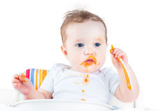 Messy baby eating her first solid vegetable food. Funny messy baby eating her first solid vegetable food in a white background Royalty Free Stock Photo