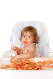 Messy baby girl eating spaghetti stock photography