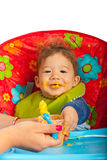 Messy baby with puree. Messy baby boy eating puree and sitting in chair Royalty Free Stock Photography