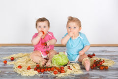 Messy baby toddlers having fun eating Stock Image