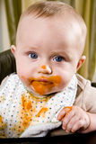 Messy baby wearing bib after eating solid food Stock Photos