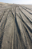 Messy beach sand with tyre tracks Royalty Free Stock Images