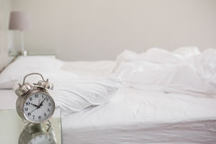 Messy bed with alarm clock on bedside table Royalty Free Stock Image