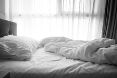 Messy bed. White pillow with blanket on bed unmade. Concept of relaxing after morning. With lighting window. Dark vignette. Black and white theme Stock Photo