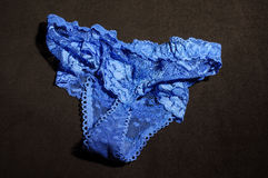 Messy blue bikini underwear on the black background Stock Images