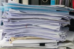 Messy business documents piles on office desk. Close up messy business documents piles on office desk royalty free stock image