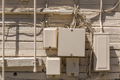 Messy cables and electrical boxes in a wooden beige wall Royalty Free Stock Image