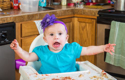 Messy Child Eating Tantrum. A talkative baby girl eating in the kitchen Stock Image