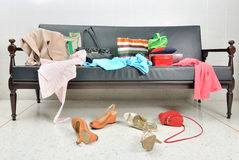Messy clothes, lady bag and shoes scattered on a sofa Stock Image