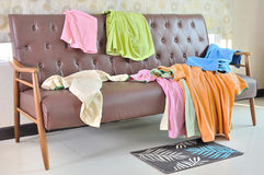 Messy clothes scattered on a sofa in room Royalty Free Stock Photography