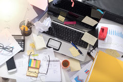 Messy and cluttered desk, light effect. Messy and cluttered office desk, light effect stock images