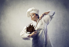 Messy cook. Funny female cook mixing and spilling everywhere some chocolate cream Stock Photos