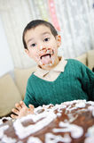 Messy cute kid. With birthday cake Royalty Free Stock Photography