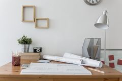 Messy desk with architect's plans. On it stock image
