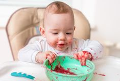 Messy and dirty baby is eating from bowl Stock Photo
