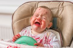 Messy and dirty baby is eating snack and crying stock image