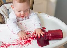 Messy and dirty baby is eating snack with hands Royalty Free Stock Photography