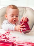 Messy and dirty baby is eating snack with hands Royalty Free Stock Image