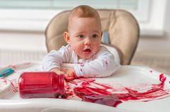 Messy and dirty baby is eating snack with hands Stock Image