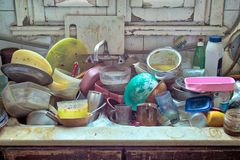 Messy Dirty Kitchen. Pile of dirty utensils in a kitchen washbasin stock photography