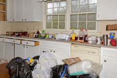 Messy Dirty Kitchen. A messy kitchen with trash bags on the floor. Concept for moving and cleaning out, or a foreclosure royalty free stock photography