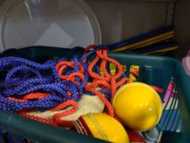A messy disorganised basket of coloured cord rope in a school games storage cupboard. Storage cupboard with yellow cricket balls and tangled string cord rope in stock photo