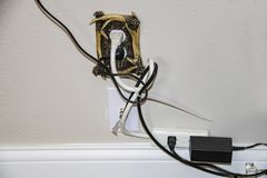 Messy electric cords - too many plugged into one decorative electrical outlet plus cable - all in a tangle stock photos