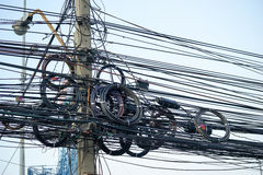 Messy electrical cables and wires on electric pole Stock Images