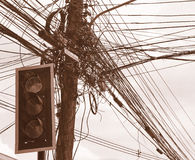 Messy electrical cables and wires on electric pole in front of the traffic lights. Royalty Free Stock Images