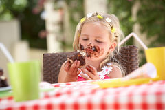 Messy Girl Eating Chocolate Cake. In Garden Royalty Free Stock Images