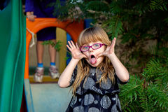 Messy Girl Making Funny Face. Blond girl with big, blue eyes and pink glasses makes a funny face for the camera.  Her hands are filthy.  Her sister is ready to Royalty Free Stock Images