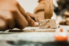 Messy hands working clay, close up and focus on potters palms with pottery Royalty Free Stock Images