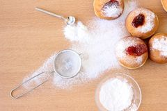 Messy Hanukkah table with sugar powder and doughnuts royalty free stock images