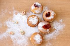 Messy Hanukkah table with sugar powder and doughnuts. And dreidels Royalty Free Stock Image